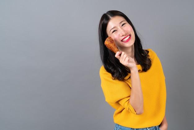 La giovane donna asiatica con la faccia felice e gode di mangiare la coscia di pollo fritto