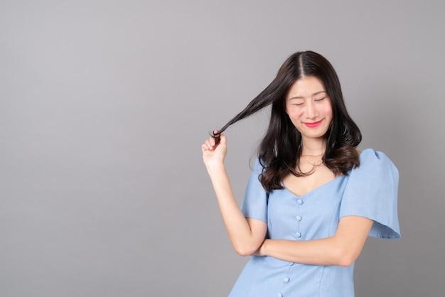 Giovane donna asiatica con la faccia felice e sorridente in abito blu