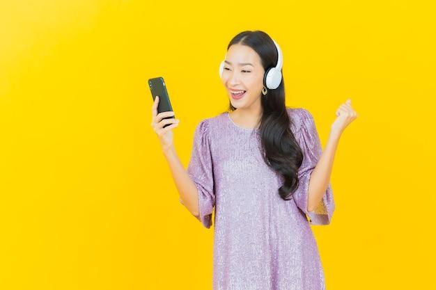 Giovane donna asiatica con cuffie e smartphone per ascoltare musica su giallo