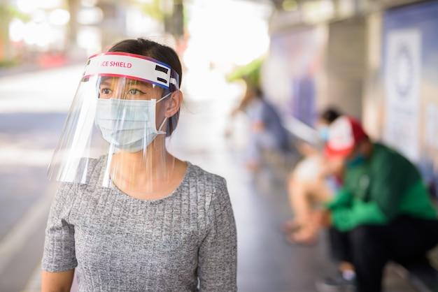 Giovane donna asiatica con maschera e visiera in attesa alla fermata dell'autobus