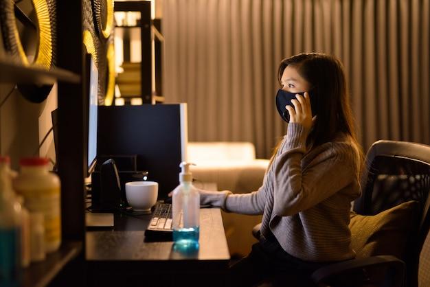 Giovane donna asiatica con maschera parlando al telefono mentre si lavora da casa durante la notte