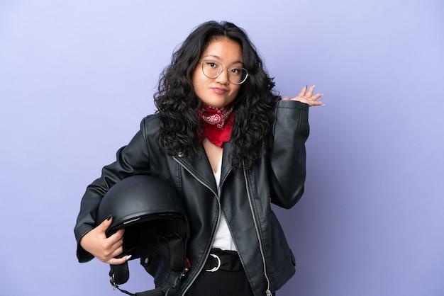 Giovane donna asiatica con un casco da motociclista isolato su sfondo viola che ha dubbi mentre alza le mani