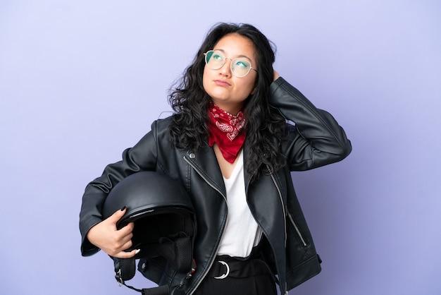 Giovane donna asiatica con un casco da motociclista isolato su sfondo viola che ha dubbi