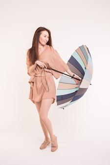 Giovane donna asiatica con ombrello multicolore sulla superficie bianca
