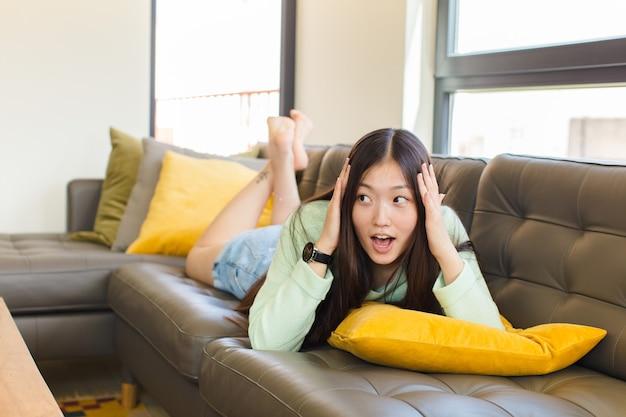 Giovane donna asiatica con la bocca aperta, che sembra inorridita e scioccata a causa di un terribile errore, alzando le mani alla testa