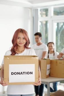 Giovane donna asiatica con i capelli rosa che tiene in mano una grande scatola di generi alimentari e vestiti che le persone hanno donato alla fondazione di beneficenza