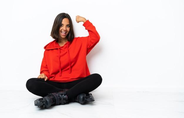 Giovane donna asiatica con pattini a rotelle sul pavimento facendo un forte gesto