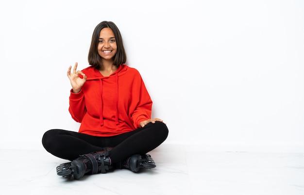 Giovane donna asiatica con pattini a rotelle sul pavimento che mostra segno giusto con le dita