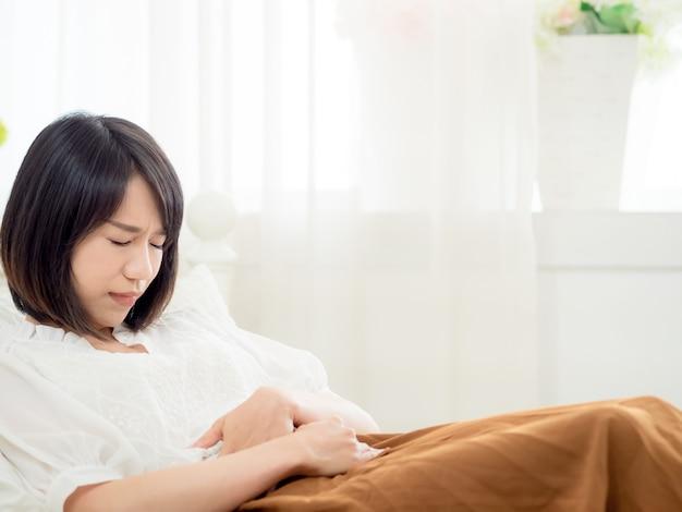 Giovane donna asiatica con mal di stomaco