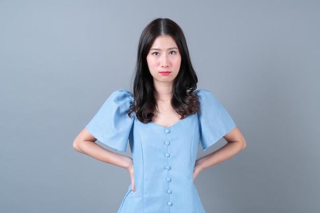 Giovane donna asiatica con il viso imbronciato in abito blu su grigio