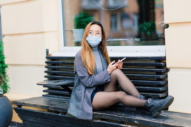 Giovane donna asiatica con maschera chirurgica per la protezione del viso. fa la pendolare tra casa e posto di lavoro in città