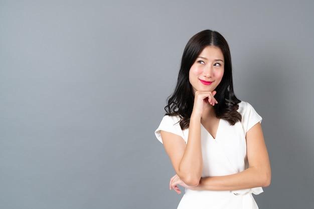 Giovane donna asiatica con la faccia pensante su grigio