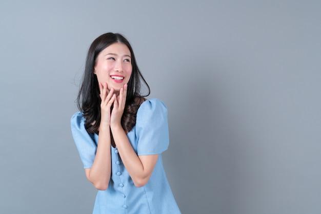 Giovane donna asiatica con il pensiero e la faccia felice in abito blu su grigio