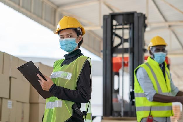La giovane lavoratrice asiatica con i lavoratori uomini indossa una maschera per proteggere il coronavirus che lavora nella fabbrica del magazzino logistico