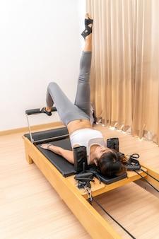 Giovane donna asiatica che lavora sulla macchina del riformatore di pilates durante la sua formazione esercizio di salute