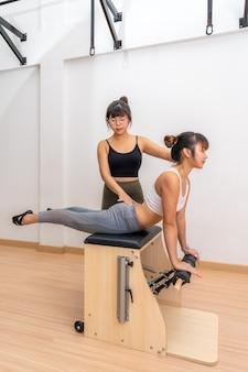 Giovane donna asiatica che lavora sulla macchina della sedia di wanda dei pilates con il suo allenatore durante la sua formazione esercizio di salute