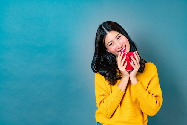 Giovane donna asiatica in maglione giallo che tiene una tazza di caffè rossa, un buon profumo e godersi il caffè su sfondo blu