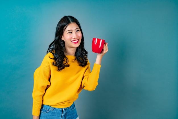 La giovane donna asiatica in maglione giallo che tiene una tazza di caffè rossa, ha un buon profumo e gode del caffè sull'azzurro