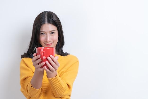 La giovane donna asiatica in maglione giallo che tiene una tazza di caffè rossa, ha un buon odore e gode del caffè su bianco