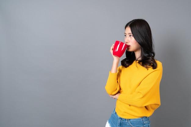 La giovane donna asiatica in maglione giallo che tiene una tazza di caffè rossa, ha un buon profumo e si gode il caffè