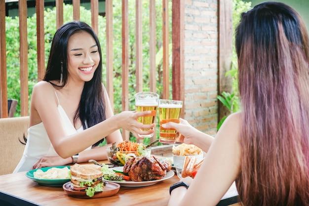 Giovani donne asiatiche che bevono i vetri del tintinnio e della birra felici mentre godendo della festa domestica