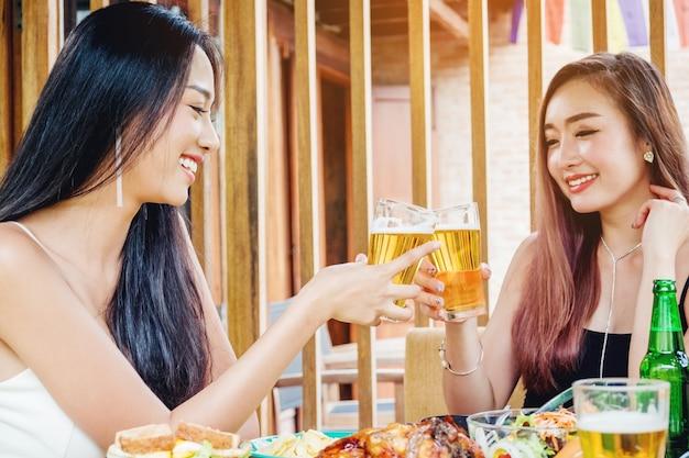 Giovani donne asiatiche che bevono bicchieri birra e tintinnio