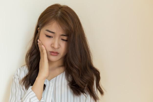 Le giovani donne asiatiche hanno denti sensibili, mal di denti, carie o gengive infiammate su sfondo chiaro. concetto di salute e malati.
