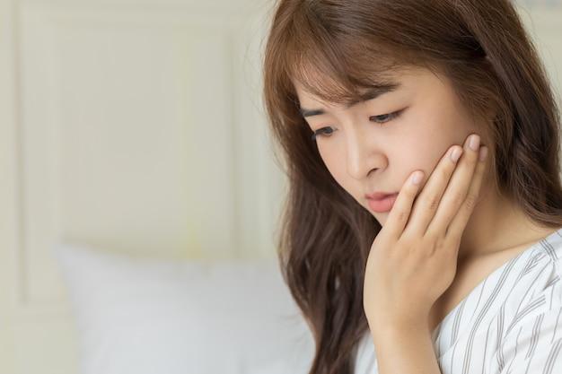Le giovani donne asiatiche hanno denti sensibili, mal di denti, carie o gengive infiammate. concetto di salute e malati.