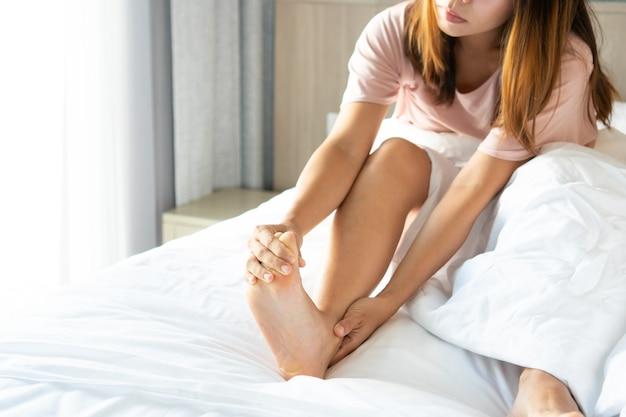 Giovani donne asiatiche con crampi ai piedi al mattino. copia spazio.