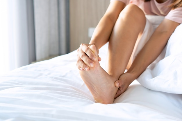 Giovani donne asiatiche con crampi ai piedi al mattino.
