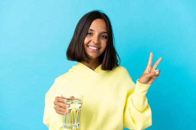 Giovane donna asiatica con un bicchiere d'acqua isolato su blu sorridente e mostrando segno di vittoria