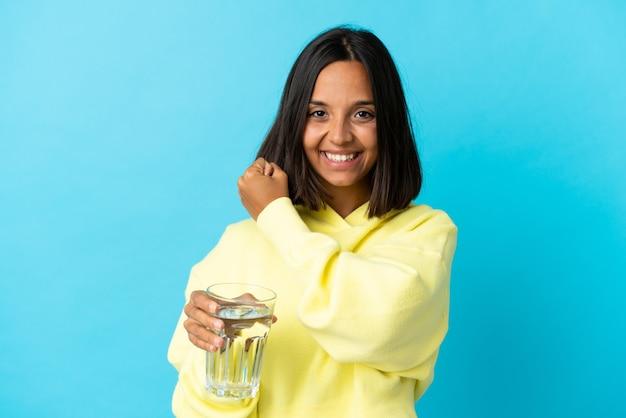 Giovane donna asiatica con un bicchiere d'acqua isolato sulla parete blu che celebra una vittoria