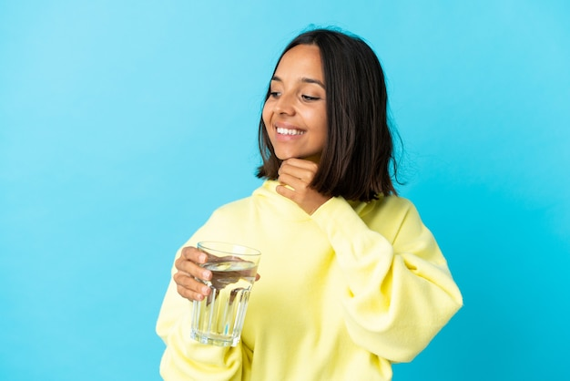 Giovane donna asiatica con un bicchiere d'acqua isolato sulla parete blu che guarda al lato e sorridente