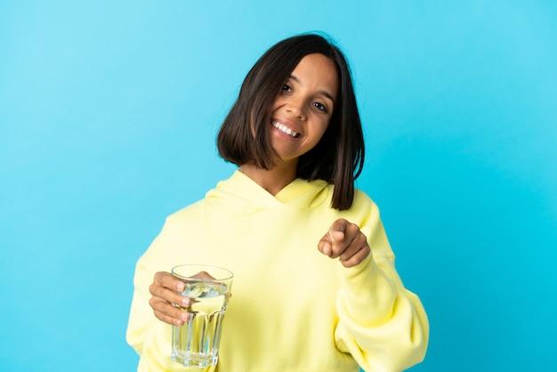 Giovane donna asiatica con un bicchiere d'acqua isolato sulla parete blu rivolto verso la parte anteriore con felice espressione