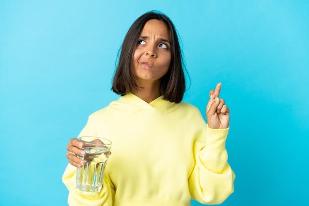 Giovane donna asiatica con un bicchiere d'acqua isolato sulla parete blu con le dita che si incrociano e che desiderano il meglio