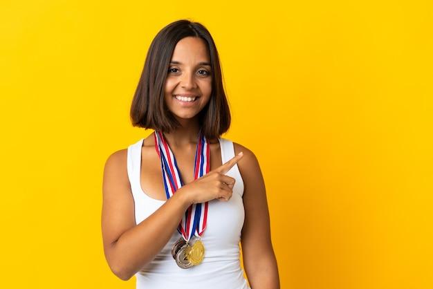 Giovane donna asiatica con medaglie isolati su sfondo bianco che punta di lato per presentare un prodotto