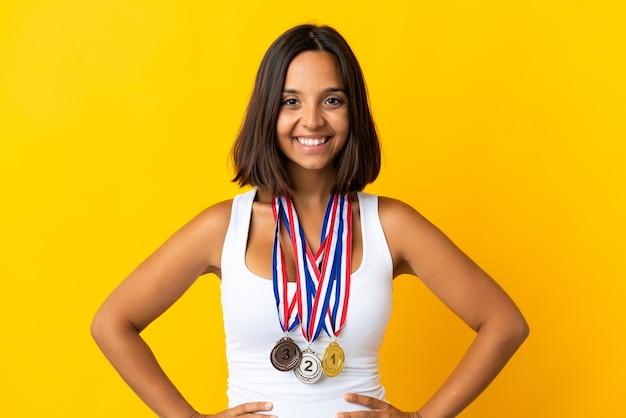 Giovane donna asiatica con medaglie isolati su sfondo bianco in posa con le braccia al fianco e sorridente