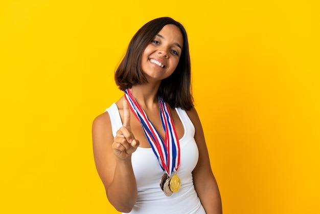 Giovane donna asiatica con medaglie su bianco che mostra e sollevando un dito