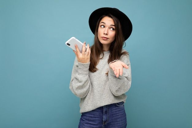 Giovane che chiede una donna bruna insoddisfatta che punta la mano su di te che indossa un cappello nero