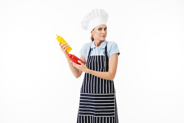 Cuoco unico stupito della giovane donna in grembiule a strisce e cappello bianco pensieroso