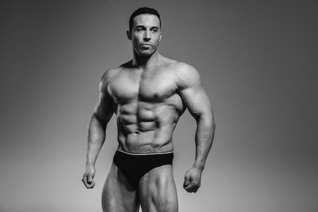 Un giovane bodybuilder atleta posa in studio in topless, mostrando i suoi addominali e muscoli. bianco e nero.