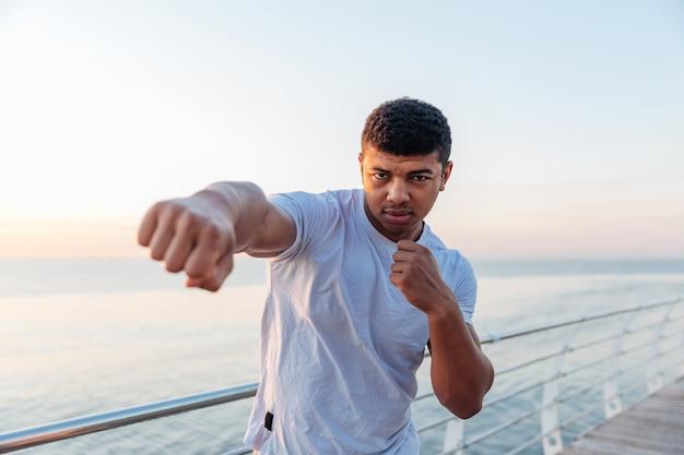 Giovane atleta che fa allenamento di boxe al mattino
