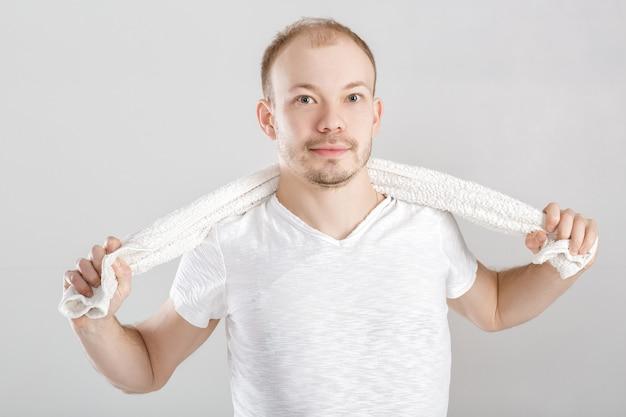 Giovane atleta che tiene un asciugamano sul grigio