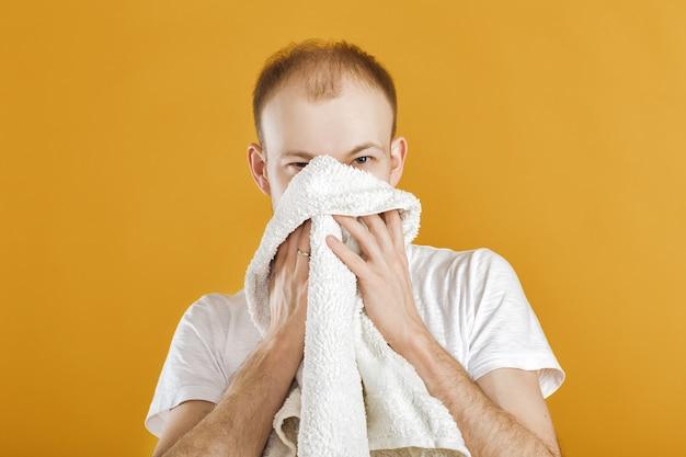 Giovane atleta che tiene un asciugamano sul giallo
