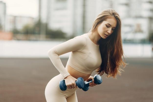 Un giovane atleta si allena con i manubri allo stadio. il concetto di una vita sana e attiva.