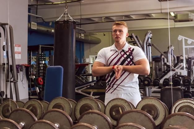 Giovane atleta che si scalda e sceglie i manubri prima di iniziare un esercizio in palestra