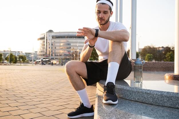 Giovane atleta in windrunner seduto per strada dopo una buona sessione di jogging al tramonto