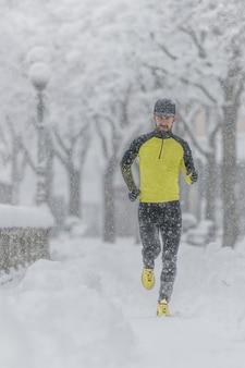 Un giovane atleta con la barba durante una corsa sulla neve