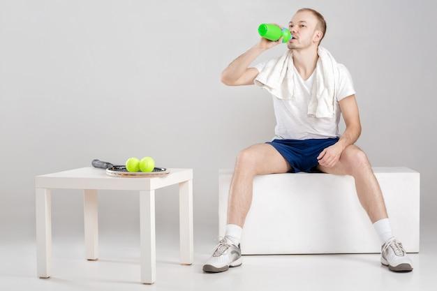 Il giovane atleta con un asciugamano beve acqua dopo un allenamento su un grigio