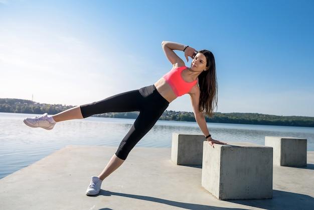 Donna giovane atleta che fa un push up vicino al lago. sport e concetti di formazione.